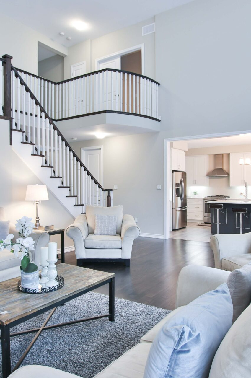 Living room with couches, coffee table and stairs with railing