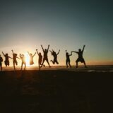 people holding hands jumping on the sunset background